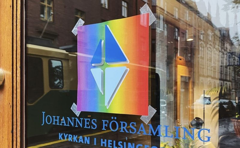 Bilden föreställer en dörr till Johannes församlings kansli. På dörren är pridefärgerna fastklistrade, i fönstret speglas en spårvagn.