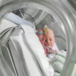 En baby ligger i en kuvös.