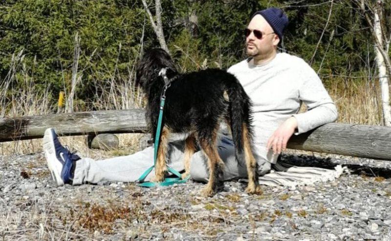 En man med solglasögon och mössa sitter på marken tillsammans med en stor hund.