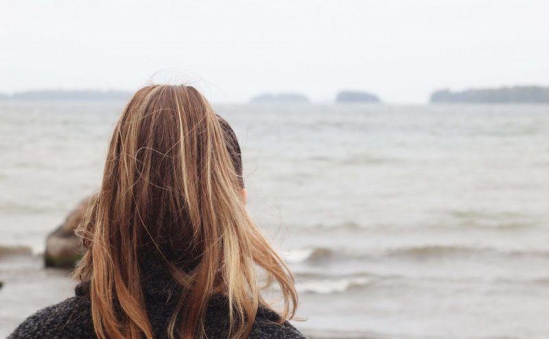 Kvinna står med ryggen mot kameran och tittar ut mot havet.