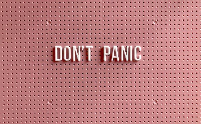 """En rosa bakgrund med texten """"Don't panic"""""""