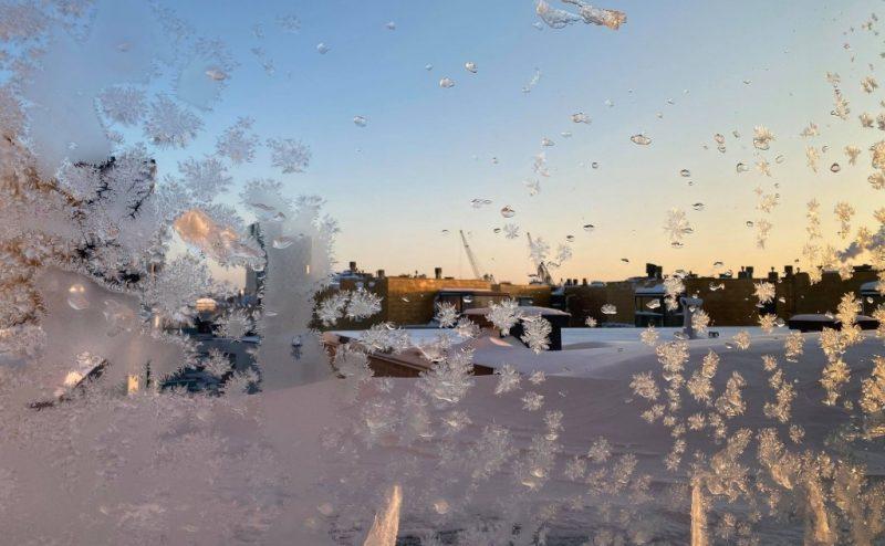 Fönster med frost och en blå himmel