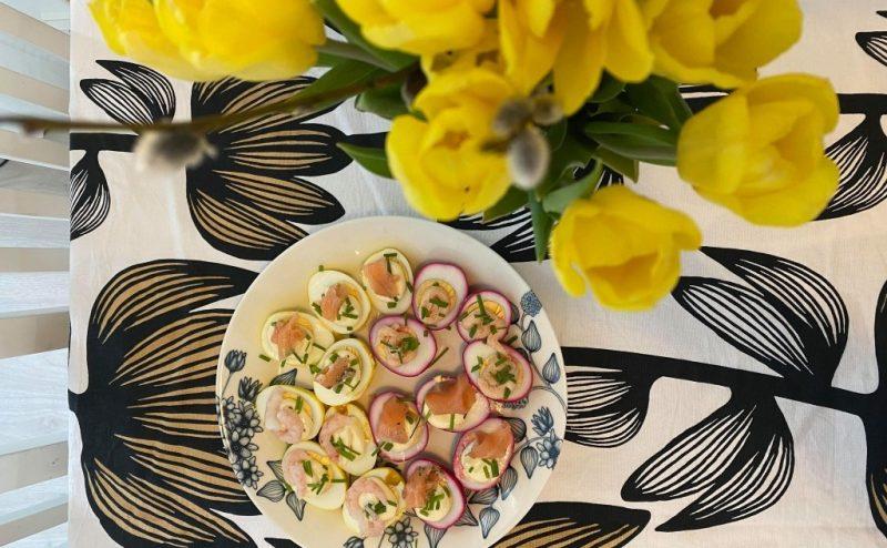 Ett fat med halverade ägg och i förgrunden gula tulpaner.