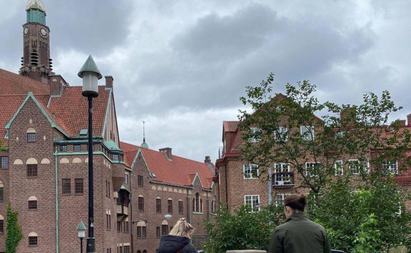 Tegelbyggnader, två personer som står med ryggarna mot kameran och en gråmolnig himmel.